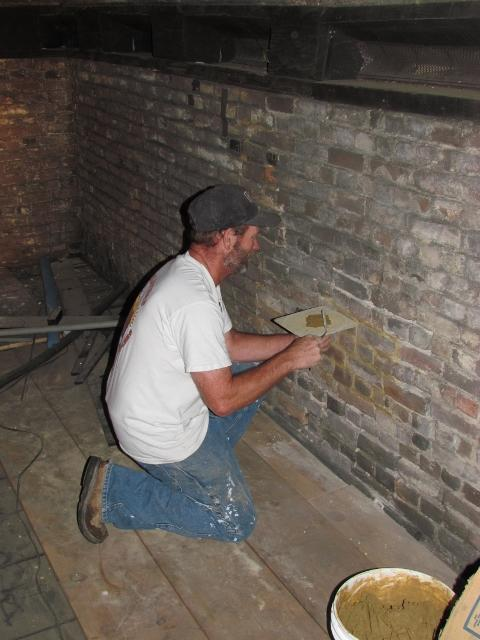 A mason repairs the mortar at the Block House as part of a comprehensive restoration and preservation project completed in 2013.