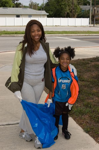 A mother and child volunteer to help pick up trash in an East Jax neighborhood clean-up.