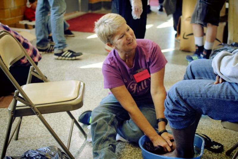 A volunteer washes the feet of a homeless person at our annual Stand Down/Project Homeless Connect event