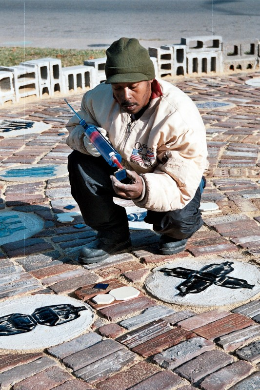 Community resident and HP employee Steve Snead works on the sundial's finishing touches.