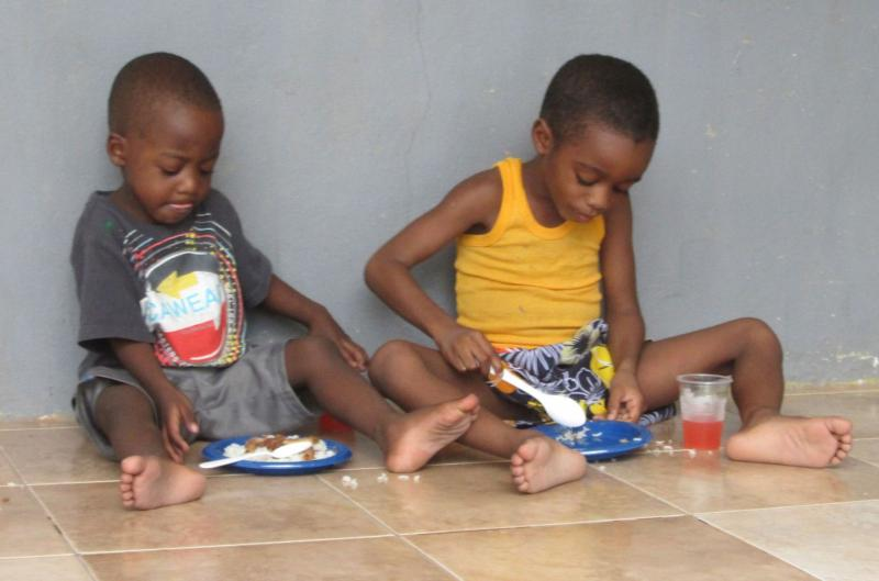 Two childen being fed at our summer program