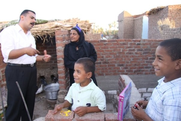 A volunteer representative visits a family to check on their well-being and needs.