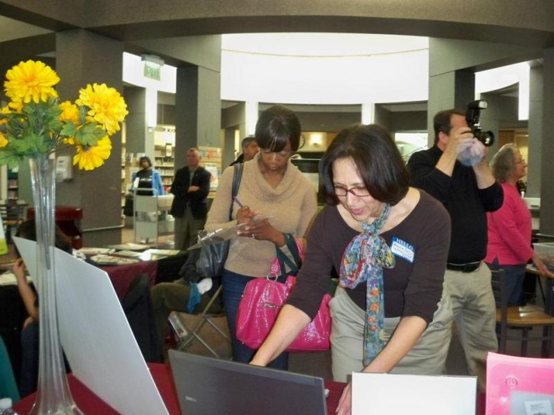 Life Coach Maria Shepard-Smith locates resources for a woman at the 2012 Money Matters Fair