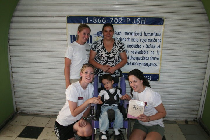 Volunteer team members working on a little girl's wheelchair