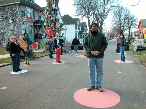 Artist/Founder Tyree Guyton poses with visitors on Heidelberg Street.
