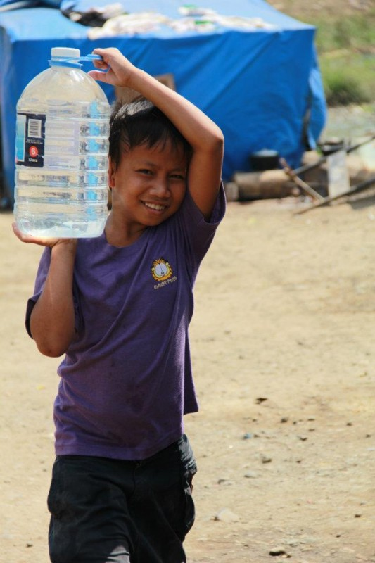 A boy carries clean water after a typhoon caused flooding in the Philippines.