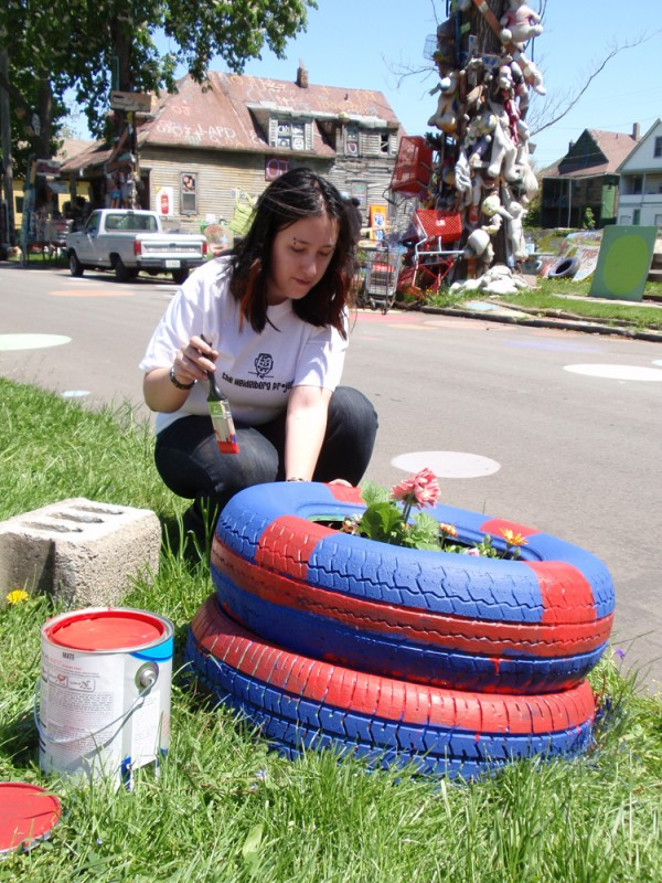 Volunteer Sarah Duncan plants flowers and paints tire planters during AmeriCorps Volunteer Day.