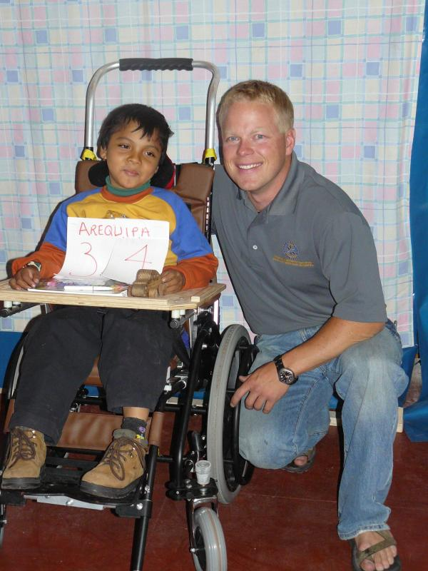 Executive Director Andrew Babcock with a child who received a ROC Chair in Arequipa, Peru.