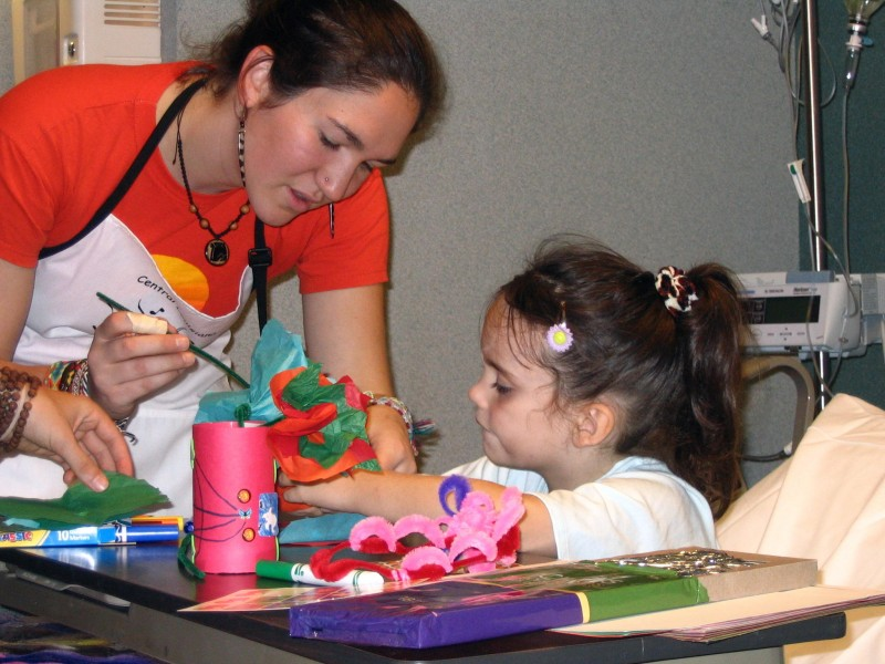 artist works with young patient at bedside