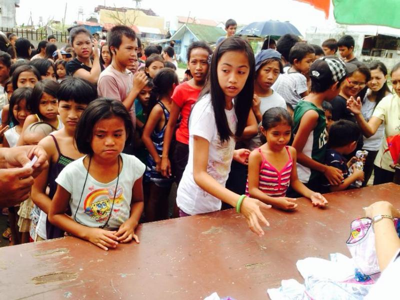 Typhoon Haiyan victims - Children waiting in line to receive relief goods - food, water and clothing being distributed by volunteers in Barangay Tu-og in Leyte.