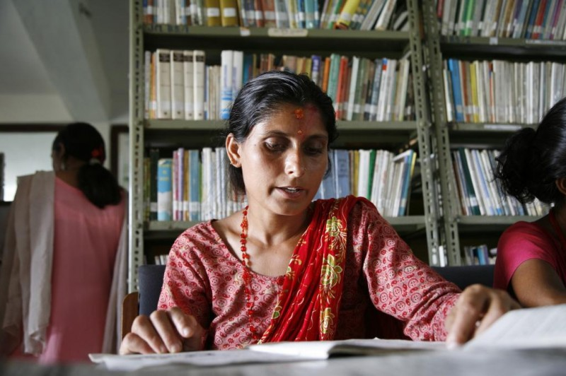 Woman reaading in a READ Center in Nepal