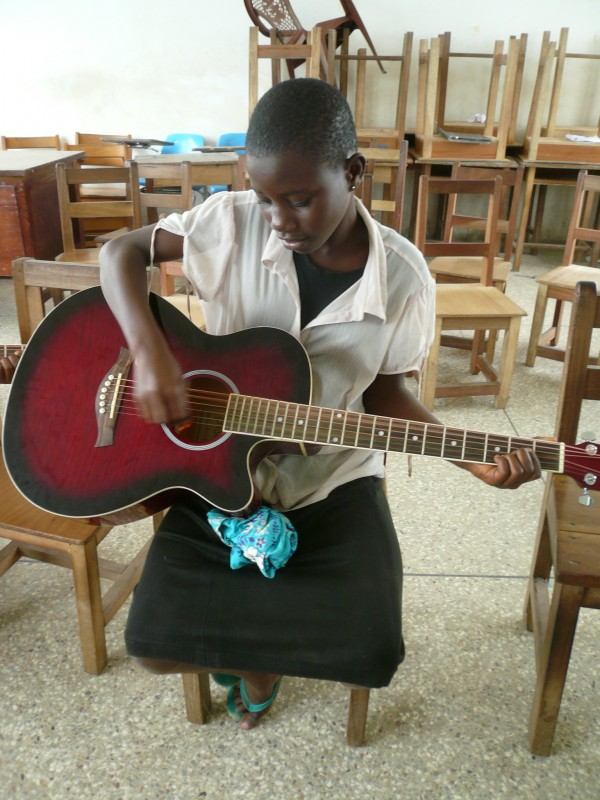 Child learning to play the guitar - Art Camp Ghana