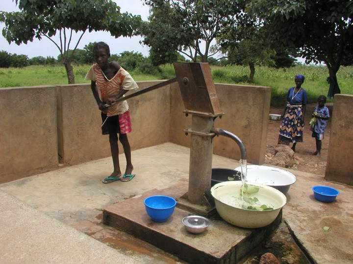 Young girl in Burkina Faso, Africa pumping clean water for her family
