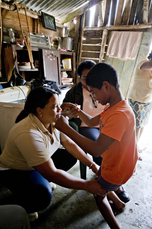 A promotora working with a child in the Community Based Rehabilitation Program for disabled children.