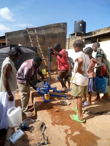 Children pumping water from rainwater harvesting system at Peace Schoo