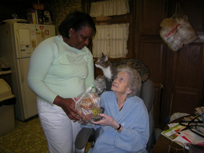 Volunteer Hyacinth visiting client June S. and her cat Scamp Casanova while delivering a meal