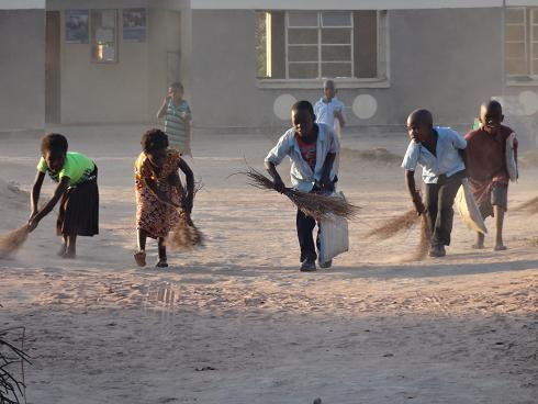 Children sweeping the school grounds at Mbula basic school