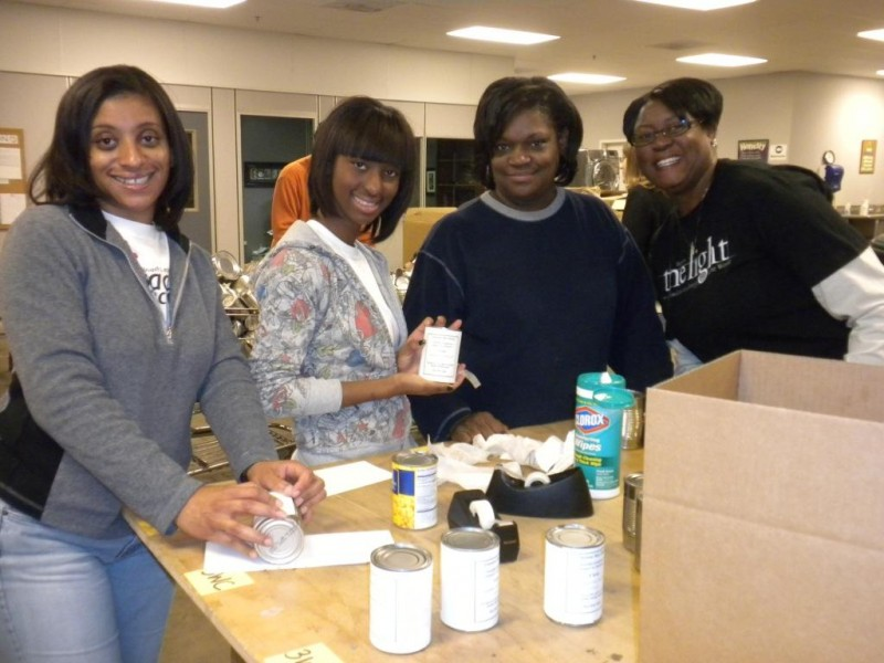 Volunteers help label canned goods.