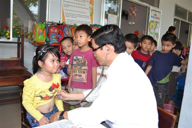 Kindergarten Children receiving health check before taking parasite medicine