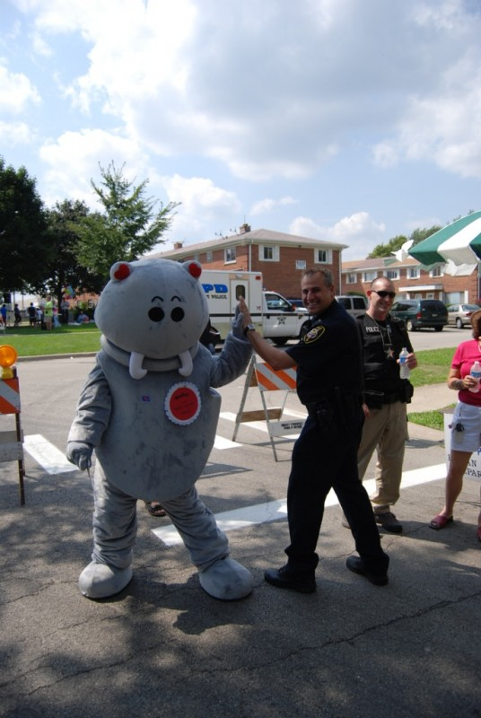 Warm-Hearted Walrus high fives a local police officer at Boxwood Bash in Mt. Prospect, IL