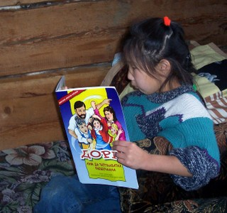 Nenets child in Siberia reading the 'Dorie' comic book