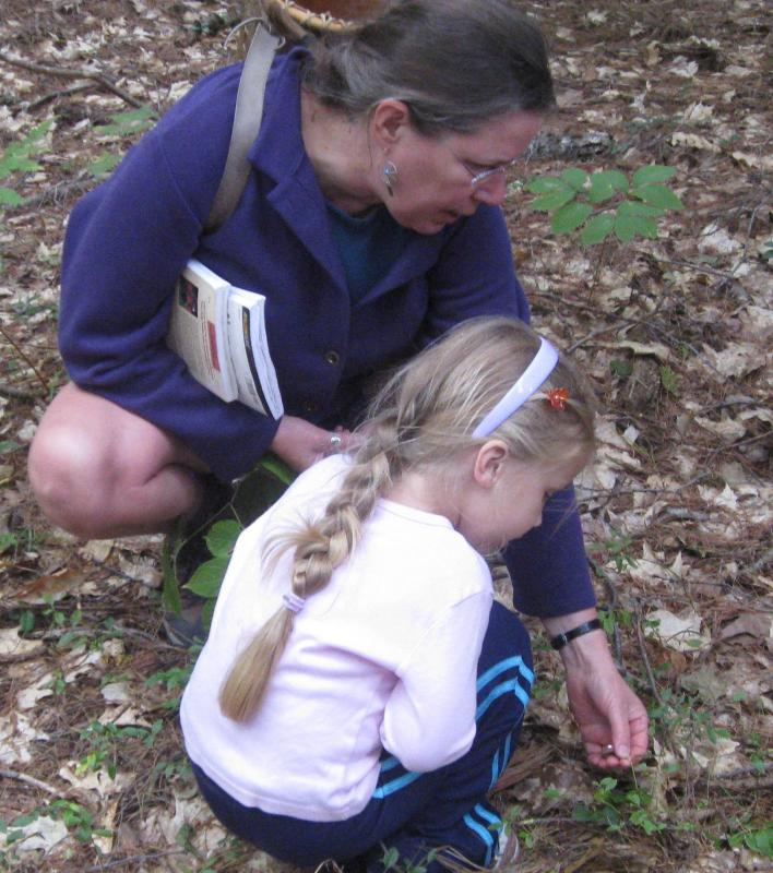 MMRG guided walk on conservation land: the leader engages a child in observing the natural world.