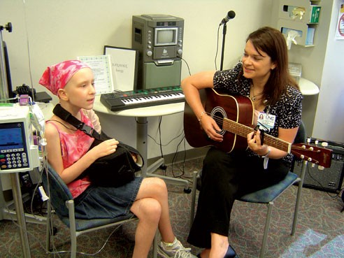 Eleanor, a child battling cancer, during a Music Therapy session