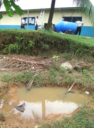 Foreground- polluted water. Behind, the OSDW team installs a rain catchment tank for a school/