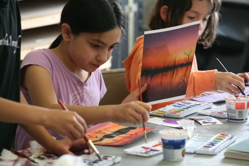 Children in Gage summer workworkshop work with watercolor to create landsscape paintings.