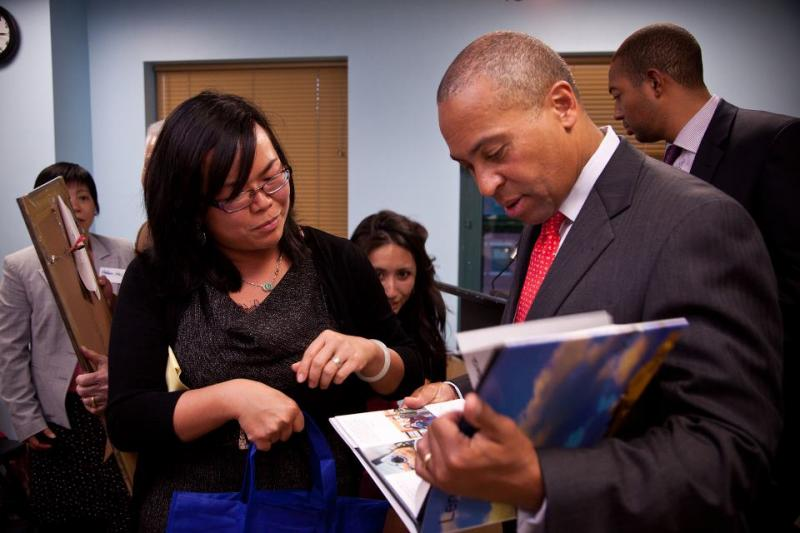 Mass Gov. Deval Patrick reads the photo book Hsu's group created.