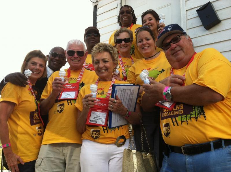 A group of AARP volunteers help installing CFL's.