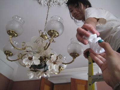 Ben Franklin student Hui Jin installs free energy efficient light bulbs in New Orleans.