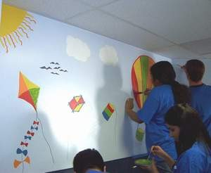 Volunteers paint a mural in the dispensing area.