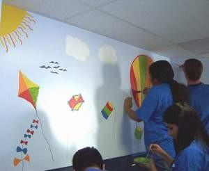 Volunteers paint a mural in the dispensing area.