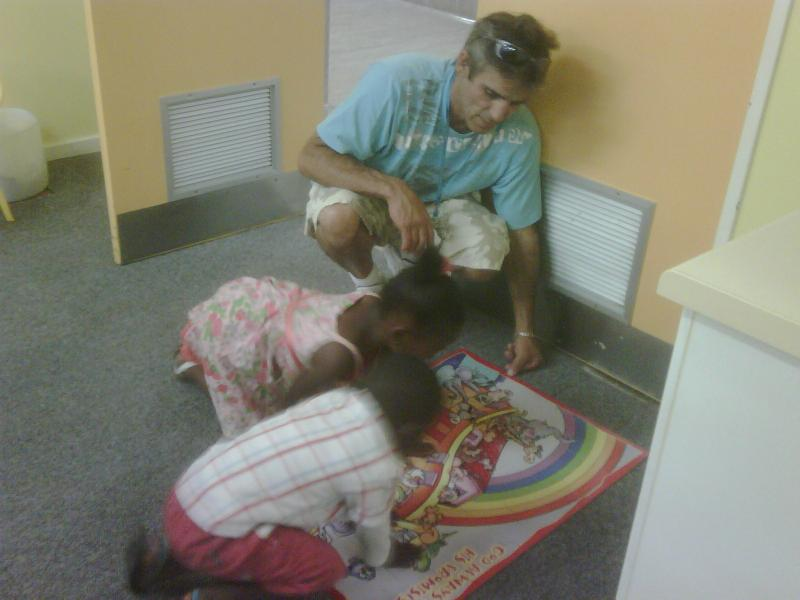 Kids at clinic helping Uncle Robert with puzzle