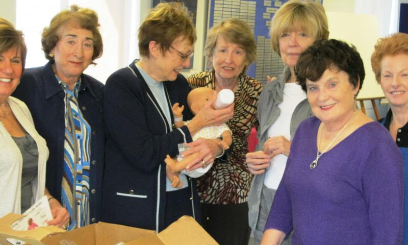 Assistance League volunteers prepare infant simulators for classroom use.