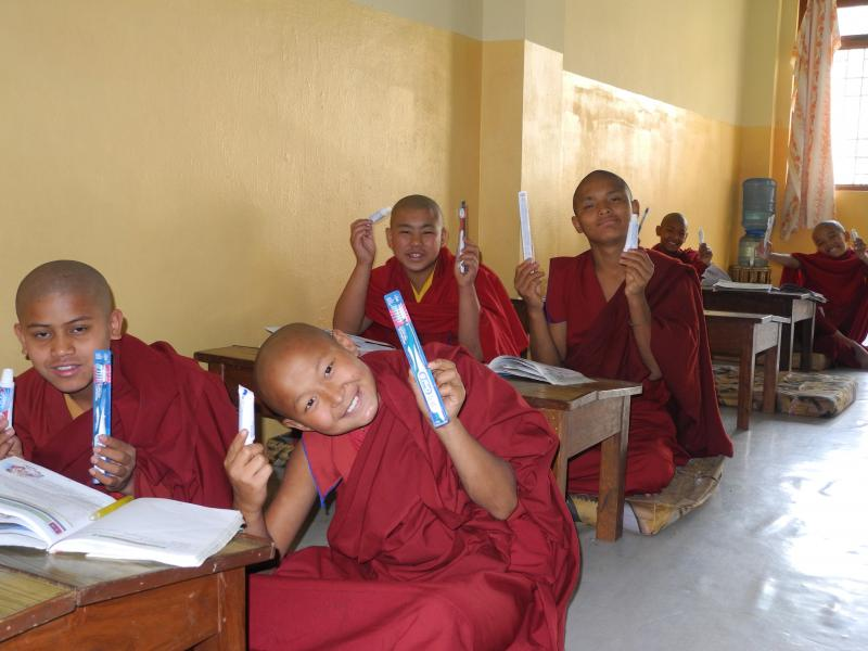 Monks receiving donation of toothbrushes.