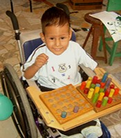 A little boy playing games on the tray of his donated wheelchair