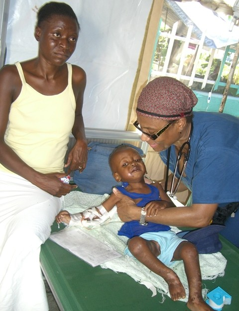 Nurse Jocelyn attending to a small Haitian boy.