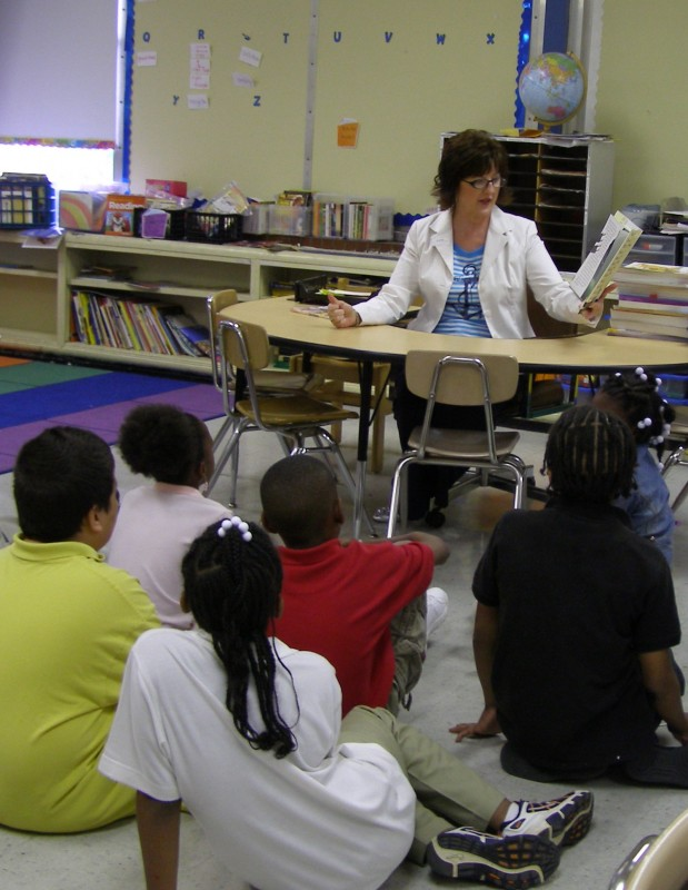 Judi Hartbarger, volunteer, reads to a group of students.