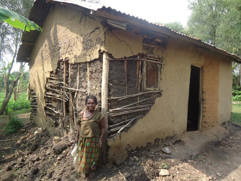 Granny Aidah in front of the house she lived in before Nyaka built her a new one