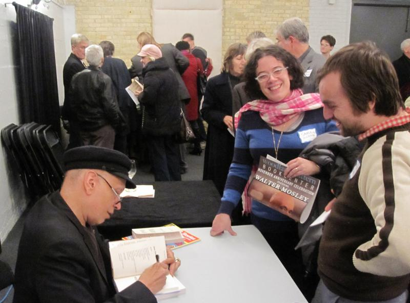Walter Mosley signs books for attendees of Woodland Pattern's 2011 November Anniversary Celebration