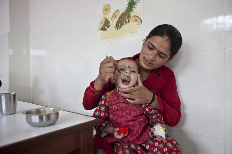 A mother feeding her child at one of NYF's 16 Nutritional Rehabilitation Homes