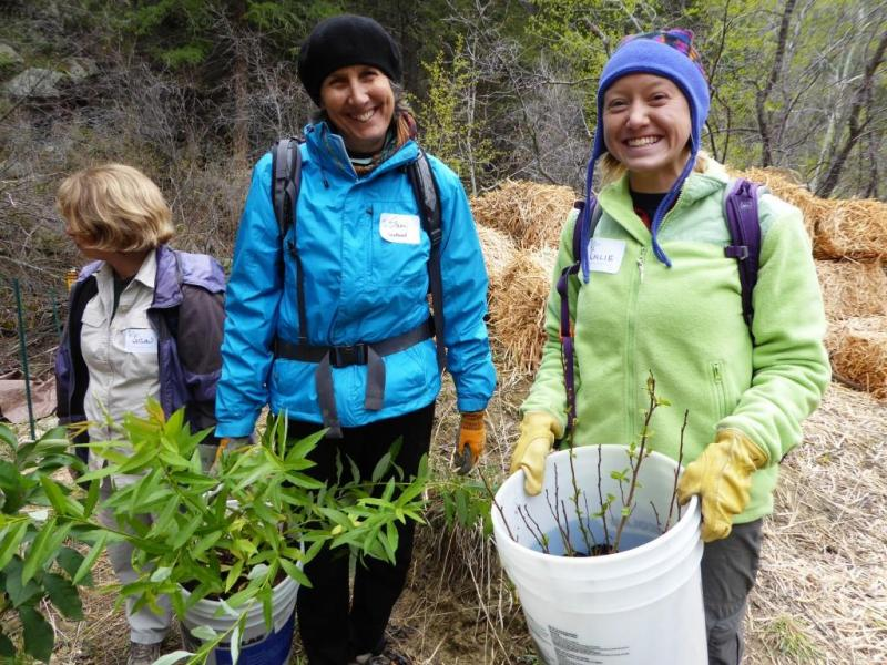 Two WRV volunteers take a moment to pose while carrying buckets of native plants at the South Saint Vrain Project, on May 15. With other volunteers, they spread mulch and planted native plants to stabilize this important waterway, which remains damaged fr