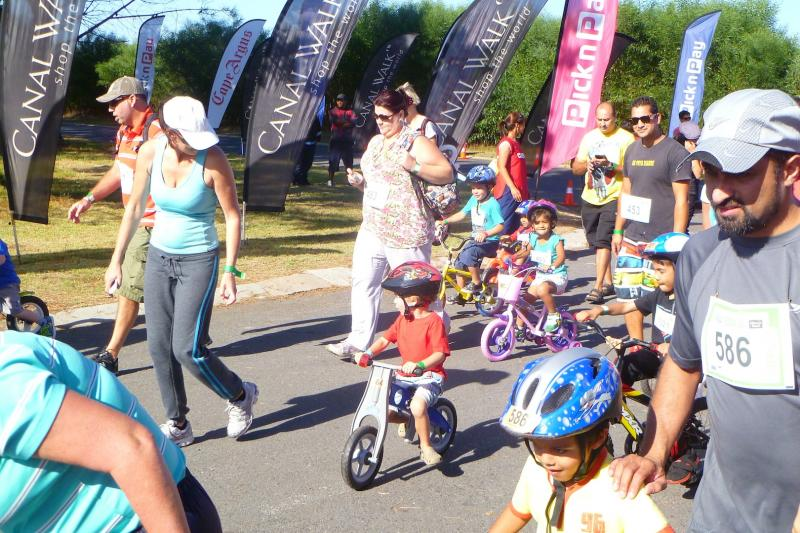 2013 Cape Argus Tricycle Tour Parents running along side of kids as co-pilots.
