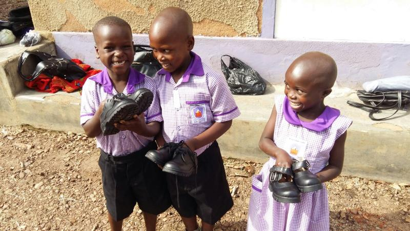 Nyaka Primary School nursery students holding their first pair of shoes.