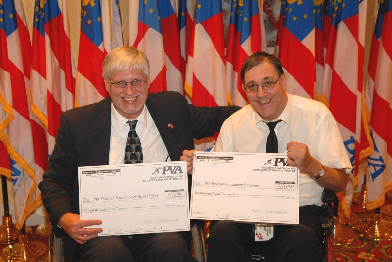 KPVA VP Jim Riemer (right) presents a check for spinal cord research to PVA President Randy Pleva