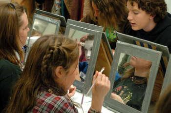 Youth learning to apply stage makeup