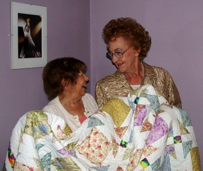 Two friends share a smile and a quilt to raise funds for motherless babies at EMBH.