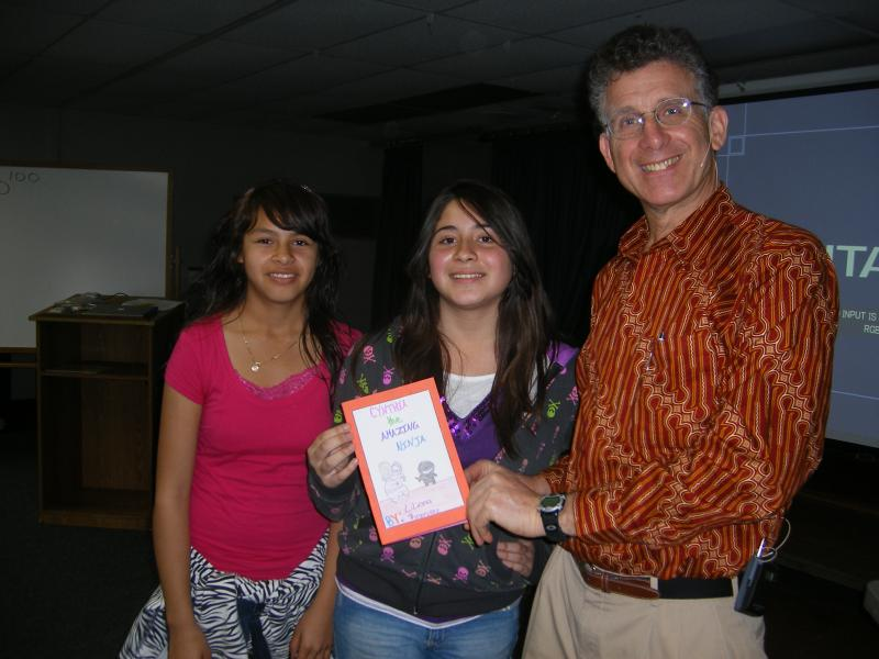 Author David Schwartz shares a moment with a student  who has written her own book.